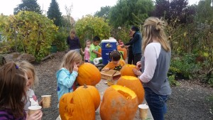 Kids carve pumpkins and enjoy homemade hot cocoa