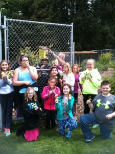 Students show off yellow kale flowers favored by many pollinator species, in front of their school garden